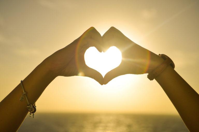Ein Herz wird mit den Händen vor einem Sonnenuntergang geformt